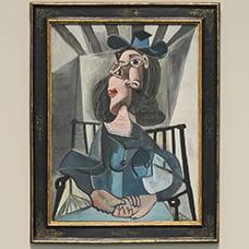 Mujer con sombrero sentada en un sillón